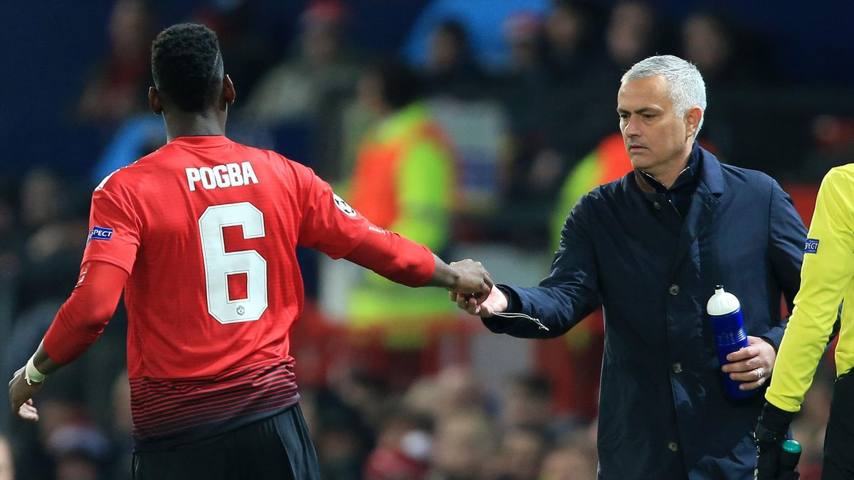 Paul Pogba of Man Utd hands a necklace over to Man Utd manager Jose Mourinho
