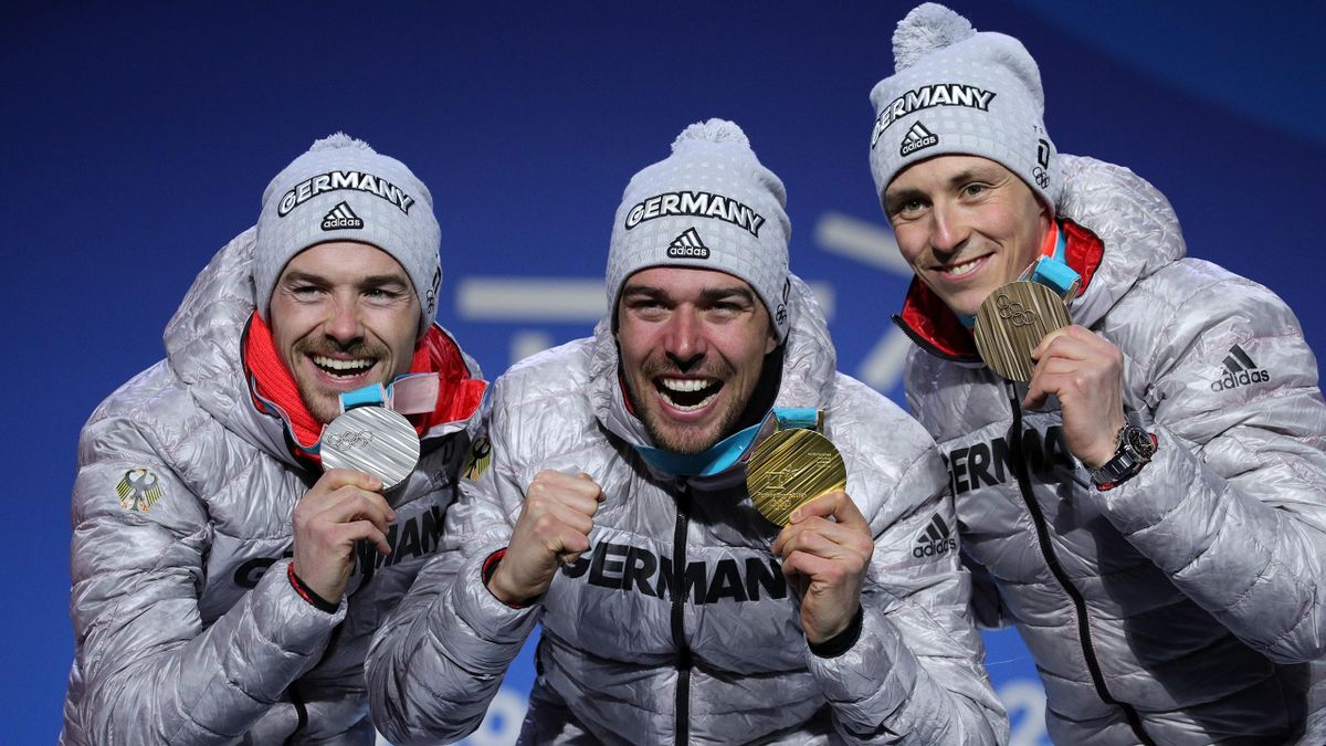 Silver medalist Fabian Riessle of Germany, gold medalist Johannes Rydzek of Germany and bronze medalist Eric Frenzel of Germany celebrate during the medal ceremony for the Nordic Combined Individual Gundersen 10km Cross-Country on day twelve of the Games.