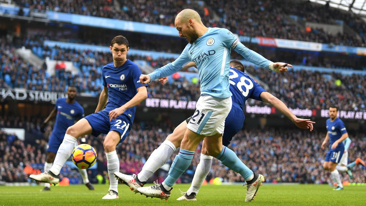 David Silva of Manchester City is challenged by Cesar Azpilicueta and Andreas Christensen of Chelsea during the Premier League match between Manchester City and Chelsea at Etihad Stadium on March 4, 2018