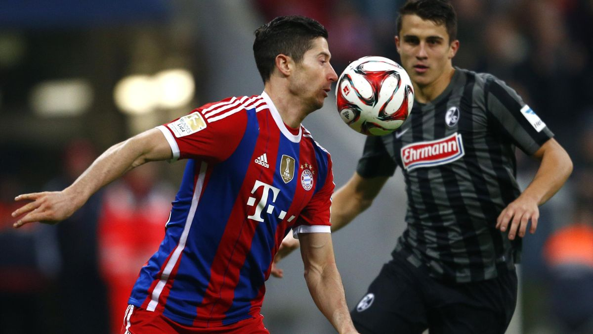 Bayern Munich's Robert Lewandowski fights for the ball with Freiburg's Marc-Oliver Kempf (Reuters)