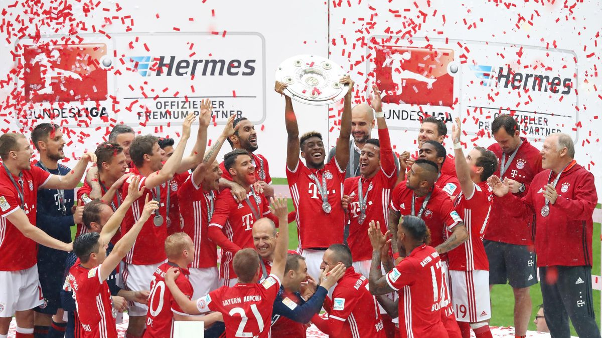 Kingsley Coman of Bayern Muenchen lifts the Meisterschale as players celebrate the Bundesliga champions after the Bundesliga match between FC Bayern Muenchen and Hannover 96
