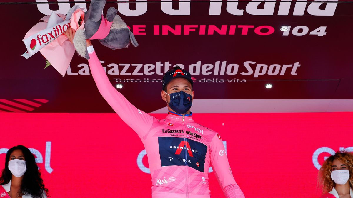 Team Ineos rider Italy's Filippo Ganna, wearing the overall leader's pink jersey, celebrates on the podium after winning the first stage of the Giro d'Italia 2021 cycling race, a 8.6 km individual time trial on May 8, 2021 in Turin