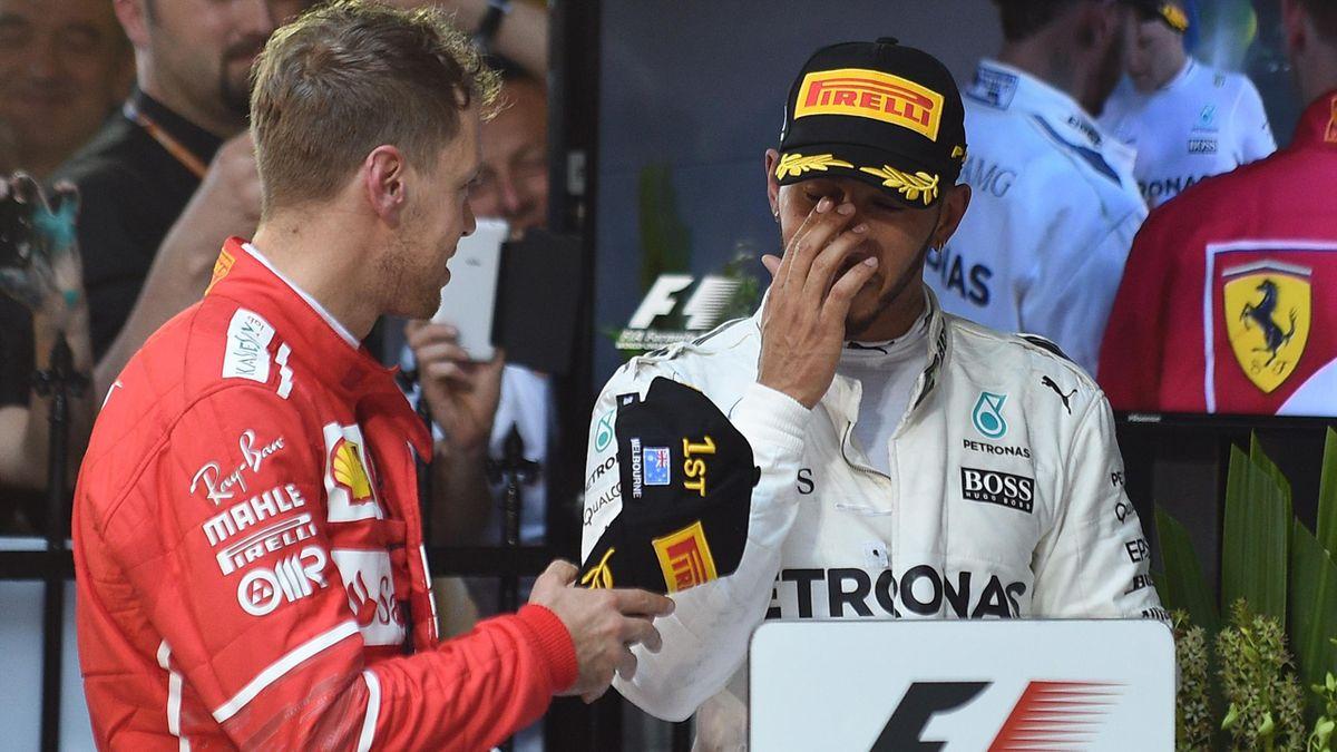 Ferrari's German driver Sebastian Vettel (L) speaks with runner-up Mercedes's British driver Lewis Hamilton