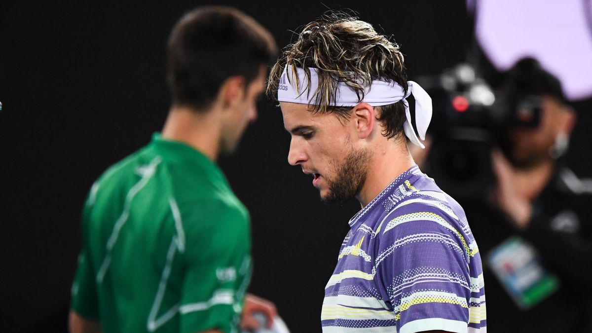 Austria's Dominic Thiem (R) and Serbia's Novak Djokovic change sides during their men's singles final match on day fourteen of the Australian Open tennis tournament in Melbourne on February 2, 2020. (Photo by William WEST / AFP) / IMAGE RESTRICTED TO EDIT