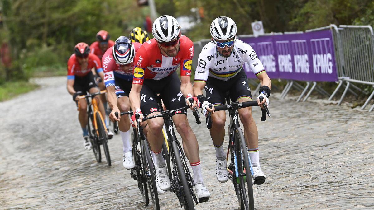 Teammates Kasper Asgreen and Julian Alaphilippe ride side-by-side up a Flandrian berg.
