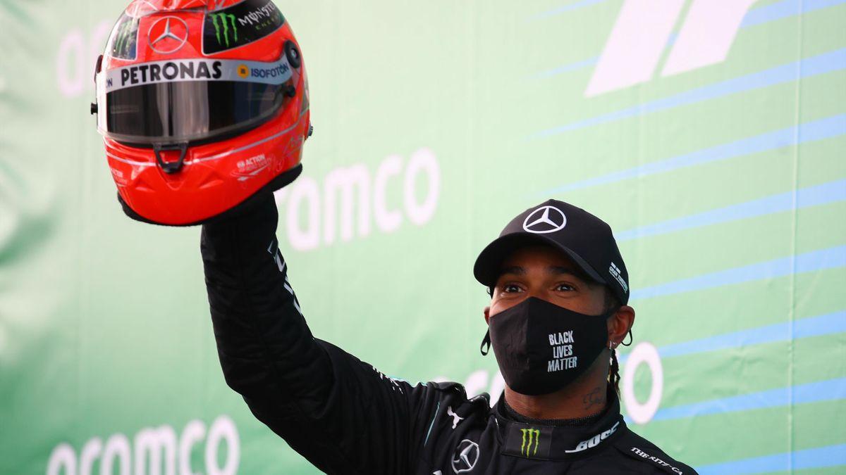Winner Mercedes' British driver Lewis Hamilton celebrates on the podium with one of Michael Schumacher's helmets