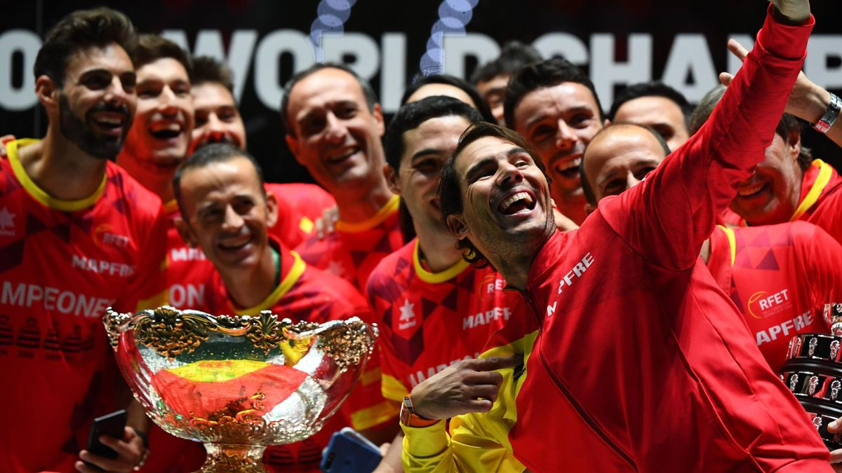 Spain's Rafael Nadal (R) takes a selfie photo posing with teammates and the winner's trophy during the trophy ceremony after winning the Davis Cup Madrid Finals