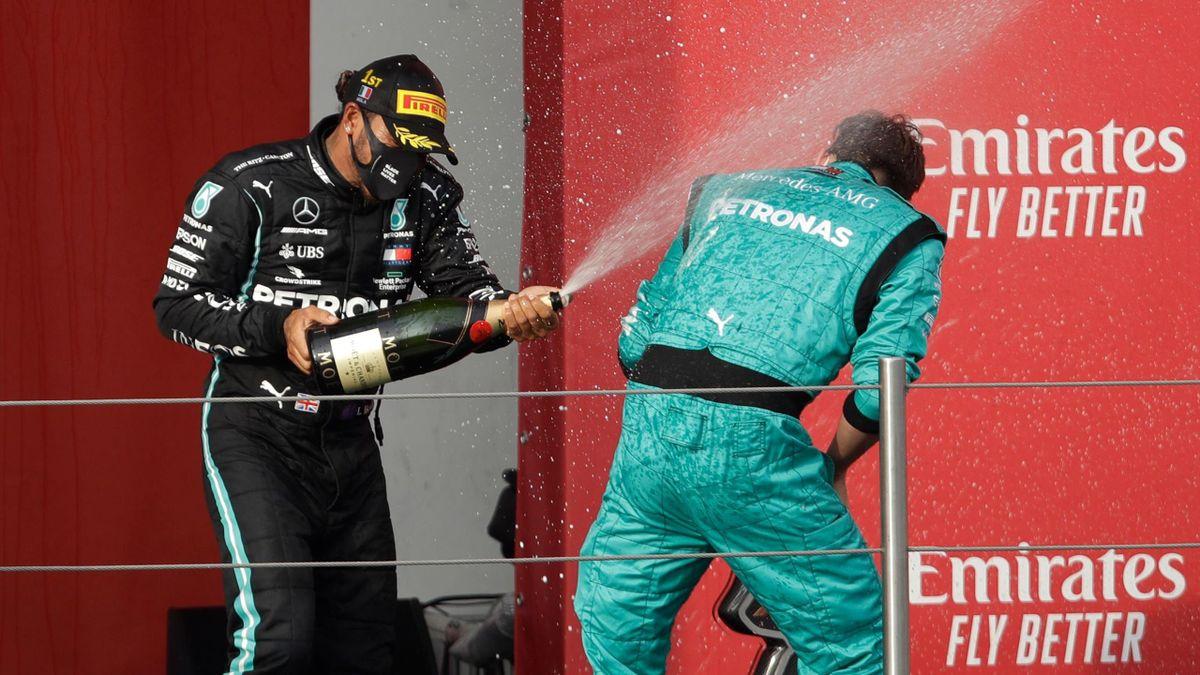 Winner Mercedes' British driver Lewis Hamilton (L) celebrates on the podium with a Mercedes F1 team mechanic