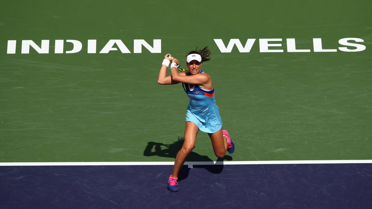 Johanna Konta of Great Britain plays a backhand against Pauline Parmentier of France during their ladies singles first round match on day three of the BNP Paribas Open at the Indian Wells Tennis Garden