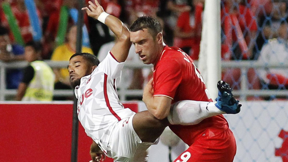 Thailand's Prathum Chutong (C) and Liverpool's Rickie Lambert in action