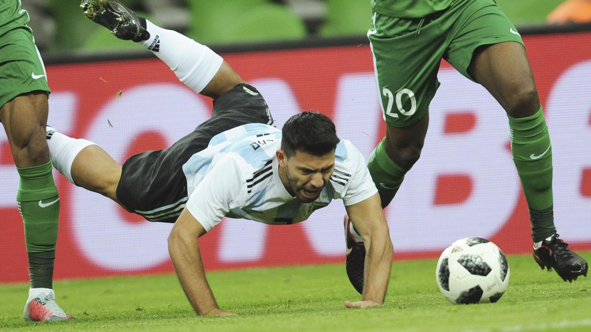 Argentina's Sergio Aguero, center, falls down as he challenges for the ball with Nigeria's Chidozie Awaziem