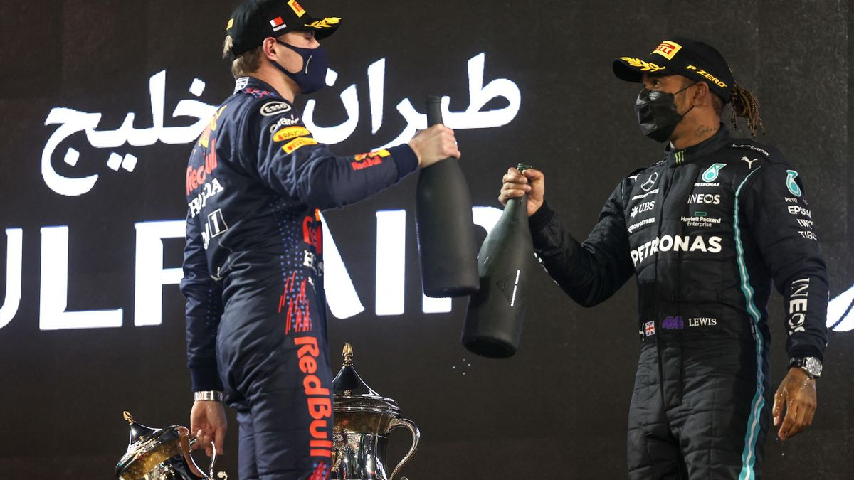 Red Bull's Dutch driver Max Verstappen greets Mercedes' British driver Lewis Hamilton on the podium after the Bahrain Formula One Grand Prix at the Bahrain International Circuit in the city of Sakhir on March 28, 2021