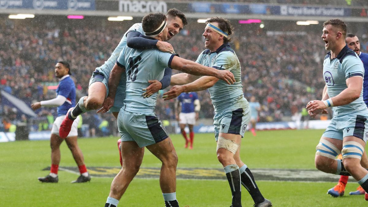 Stuart McInally of Scotland celebrates with teammates Adam Hastings and Hamish Watson after scoring his sides third try during the 2020 Guinness Six Nations match between Scotland and France at Murrayfield on March 08, 2020 in Edinburgh, Scotland