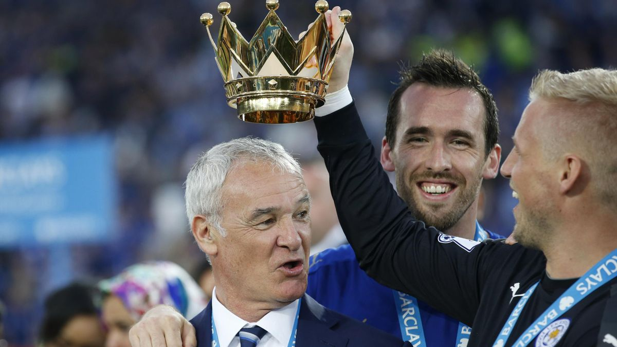 Leicester City manager Claudio Ranieri lifts the trophy with Kasper Schmeichel and Christian Fuchs as they celebrate winning the Barclays Premier League