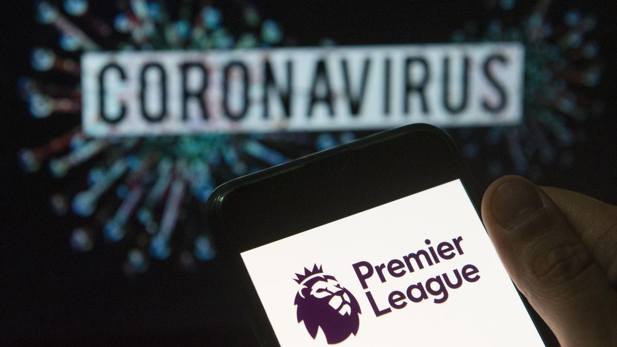 In this photo illustration the top level of the English football league Premier League logo seen displayed on a smartphone with a computer model of the COVID-19 coronavirus on the background.