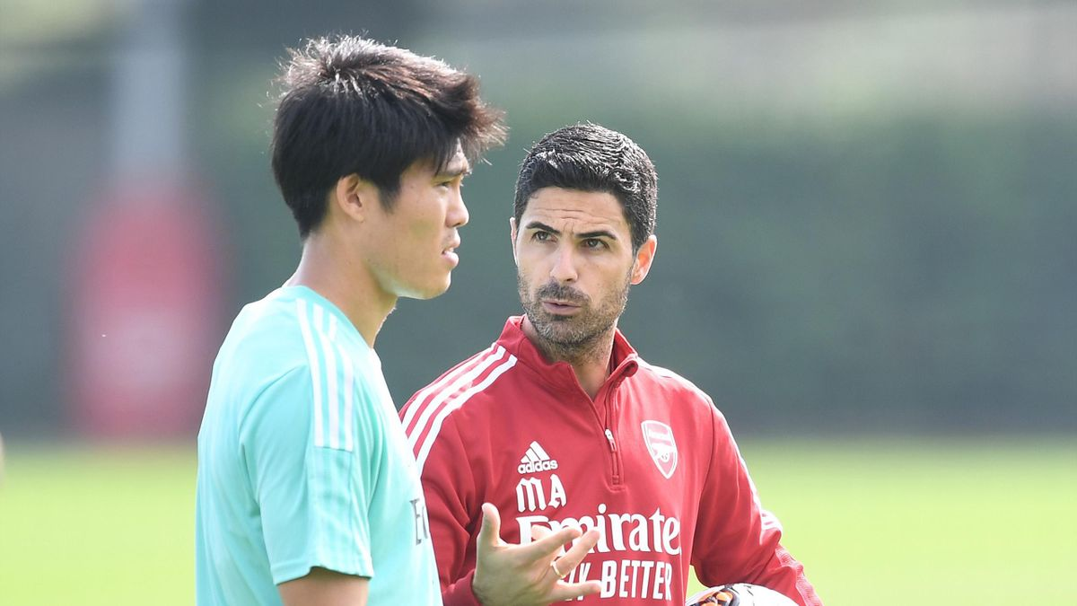 Arsenal manager Mikel Arteta talks to Takehiro Tomiyasu during a training session