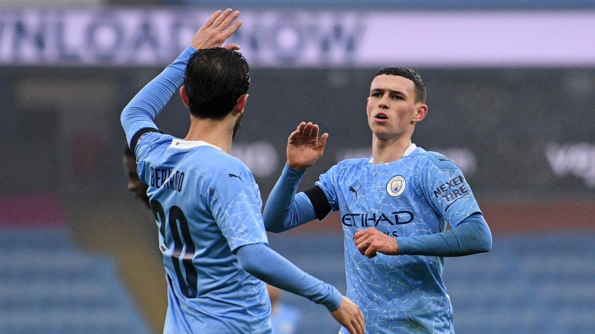 Manchester City's English midfielder Phil Foden (R) celebrates with Manchester City's Portuguese midfielder Bernardo Silva (L) after scoring their third goal during the English FA Cup third round football match between Manchester City and Birmingham City