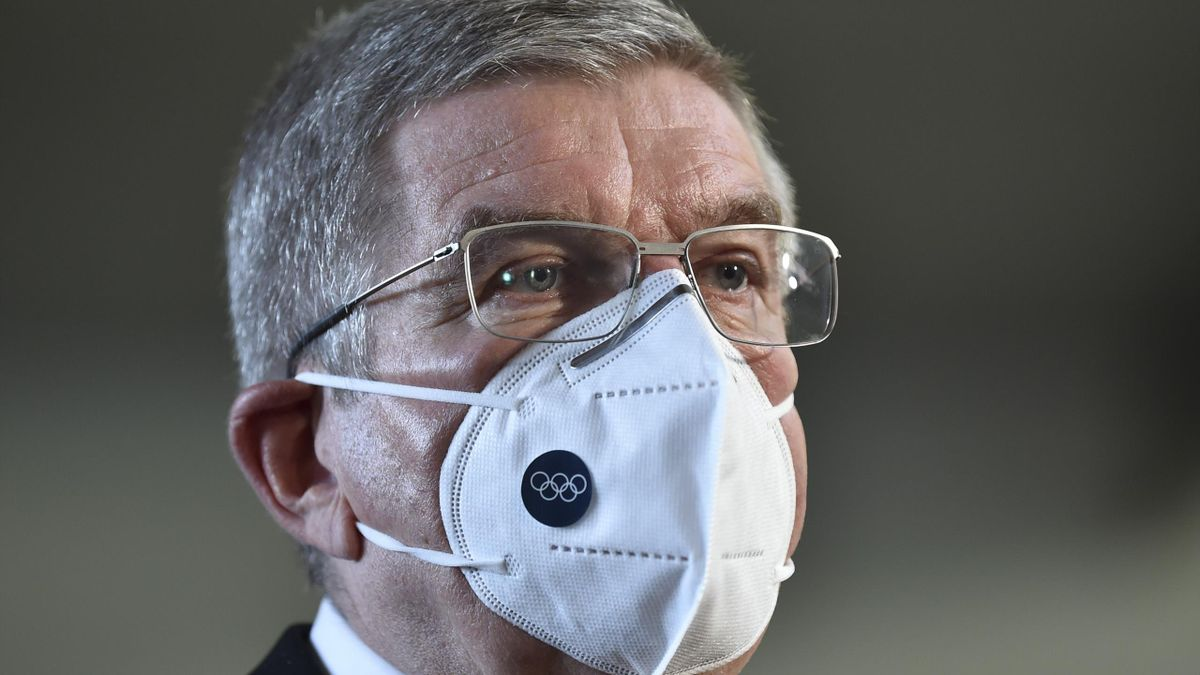 International Olympic Committee (IOC) president Thomas Bach wearing a face mask speaks to the media after his meeting with Japan's prime minister in Tokyo on November 16, 2020