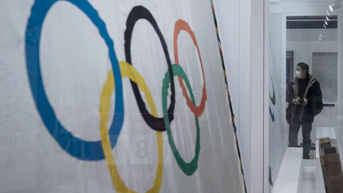 A man wearing a face mask looks at a display of Olympic flags at the Tokyo Metropolitan Government building on February 26, 2020 in Tokyo, Japan