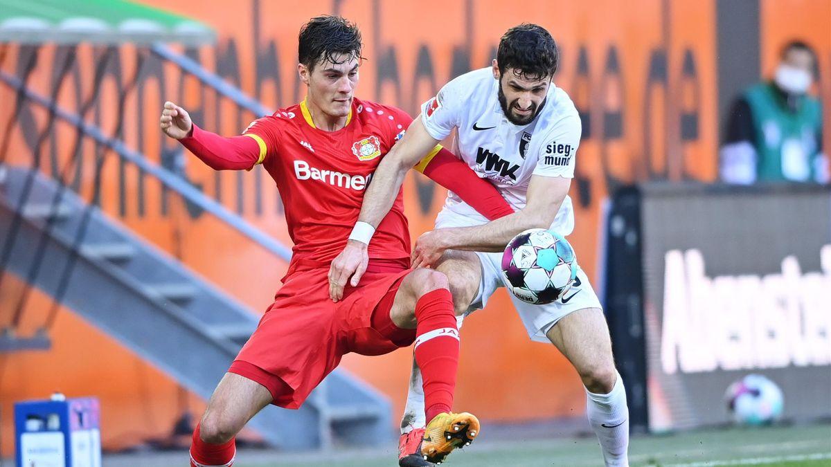 Patrik Schick (links; Bayer Leverkusen) im Zweikampf mit Daniel Caligiuri (FC Augsburg)