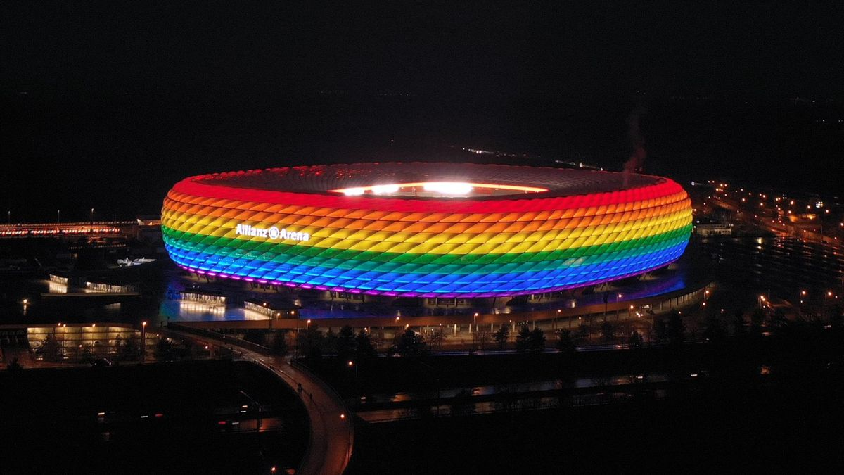 """A drone image shows the Allianz Arena soccer stadium illuminated in rainbow colours during the Bundesliga match between FC Bayern Muenchen and TSG Hoffenheim on January 30, 2021 in Munich, Germany. On the occasion of the """"Remembrance Day in German Footbal"""