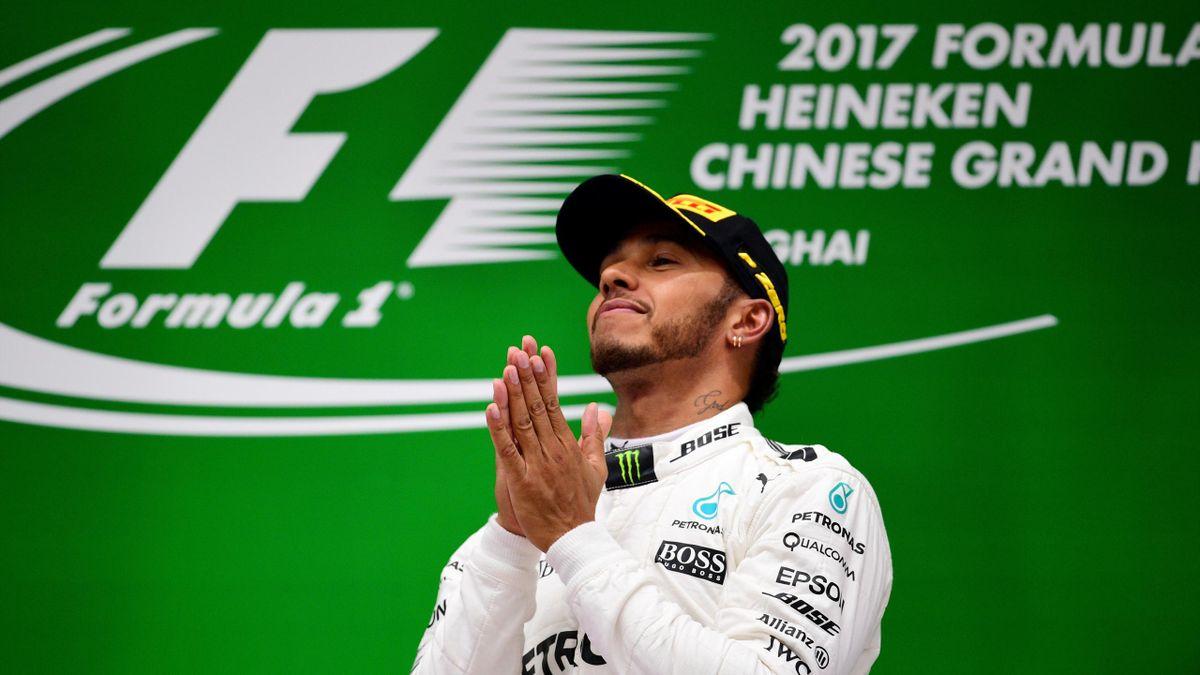 Mercedes' British driver Lewis Hamilton celebrates on the podium