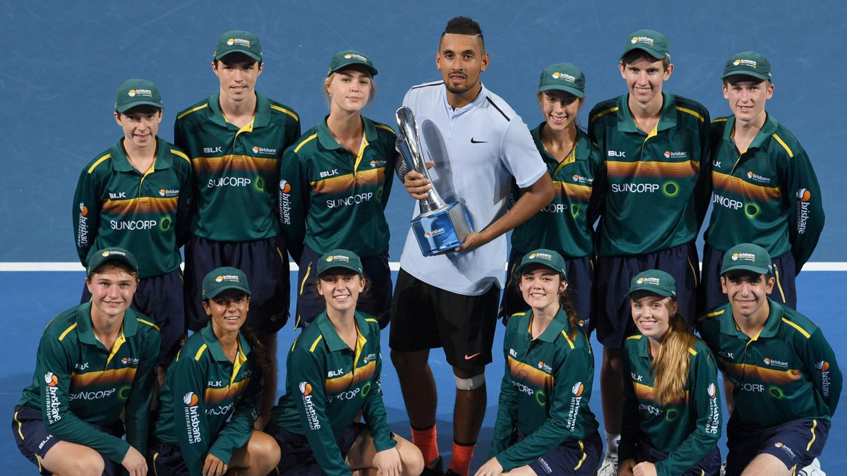 Nick Kyrgios of Australia holds the trophy with the ball boys and girls after beating Ryan Harrison of the US to win the men's singles final at the Brisbane International tennis tournament at the Pat Rafter Arena in Brisbane