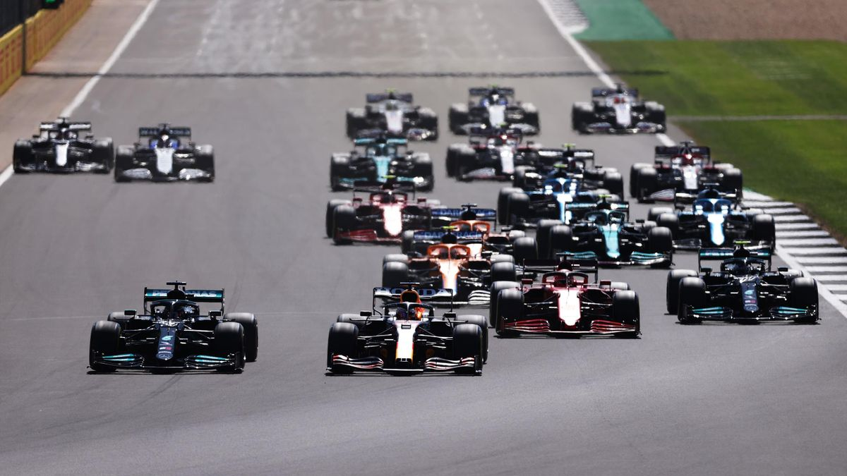 NORTHAMPTON, ENGLAND - JULY 18: Lewis Hamilton of Great Britain driving the (44) Mercedes AMG Petronas F1 Team Mercedes W12 and Max Verstappen of the Netherlands driving the (33) Red Bull Racing RB16B Honda lead the field into turn one at the start during