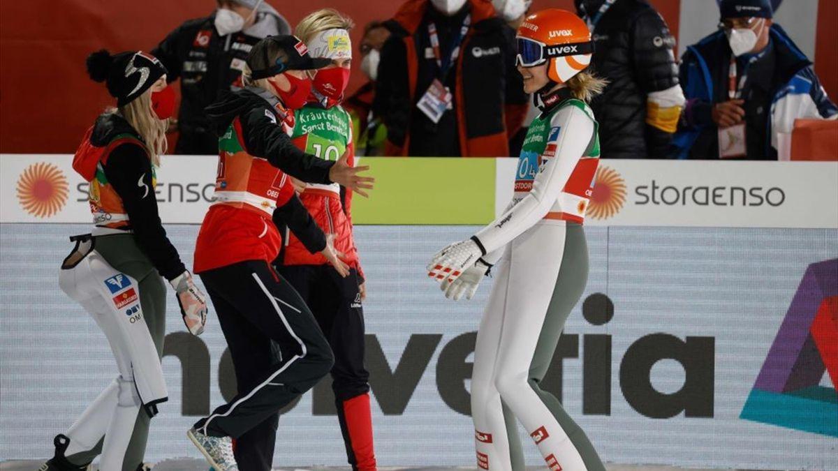Marita Kramer (r.) wird von ihren jubelnden Teamkolleginnen Daniela Iraschko-Stolz (2. v. l.), Chiara Hölzl (l.) und Sophie Sorschag in Empfang genommen