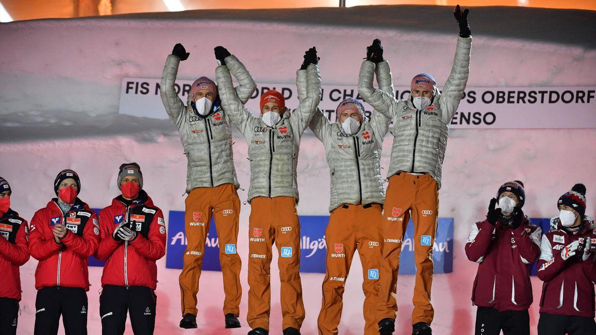 Pius Paschke, Markus Eisenbichler, Severin Freund und Karl Geiger (v. l. n. r.) mit einem Freudensprung bei der Siegerehrung in Oberstdorf nach WM-Gold im Team