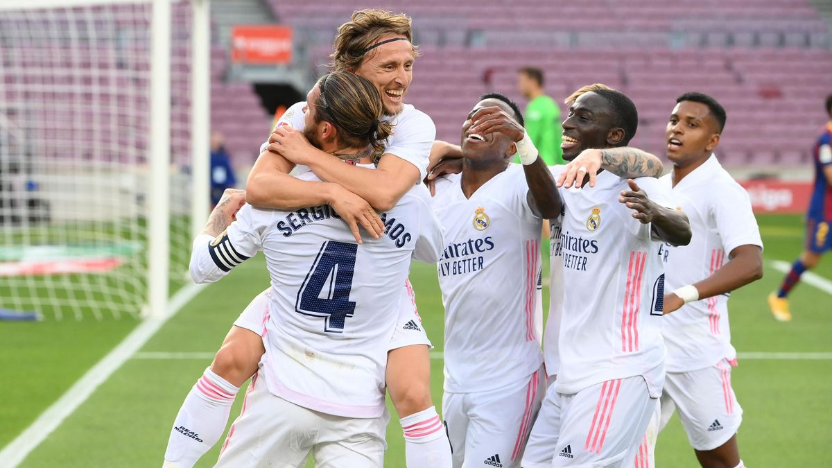 Real Madrid's Croatian midfielder Luka Modric (C) celebrates with teammates after scoring a goal during the Spanish League football match between Barcelona and Real Madrid at the Camp Nou stadium in Barcelona on October 24, 2020.