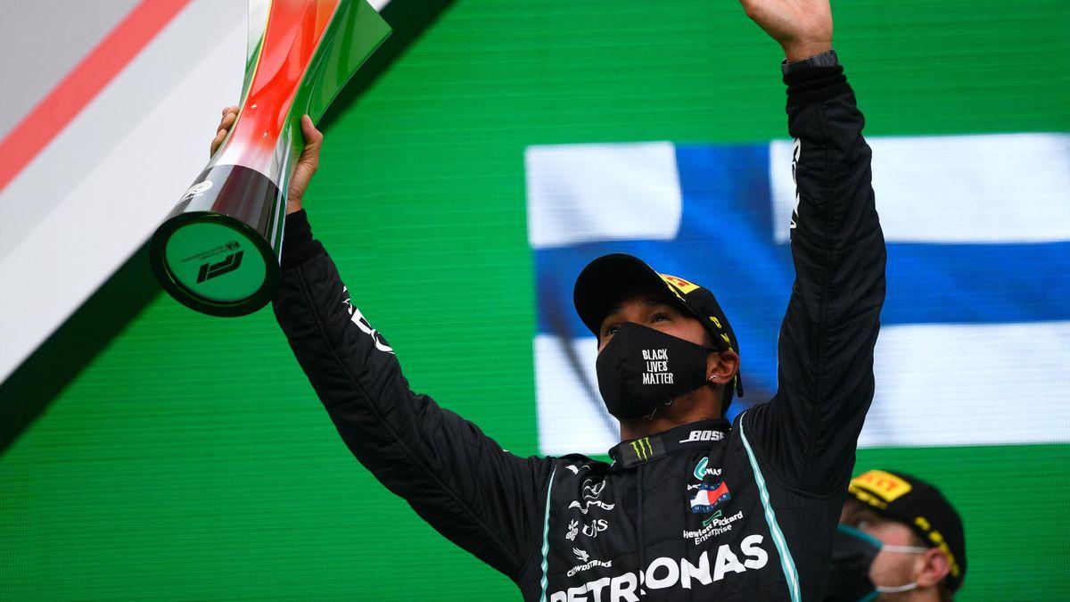 Mercedes' British driver Lewis Hamilton celebrates on the podium with the trophy after winning the Portuguese Formula One Grand Prix at the Autodromo Internacional do Algarve