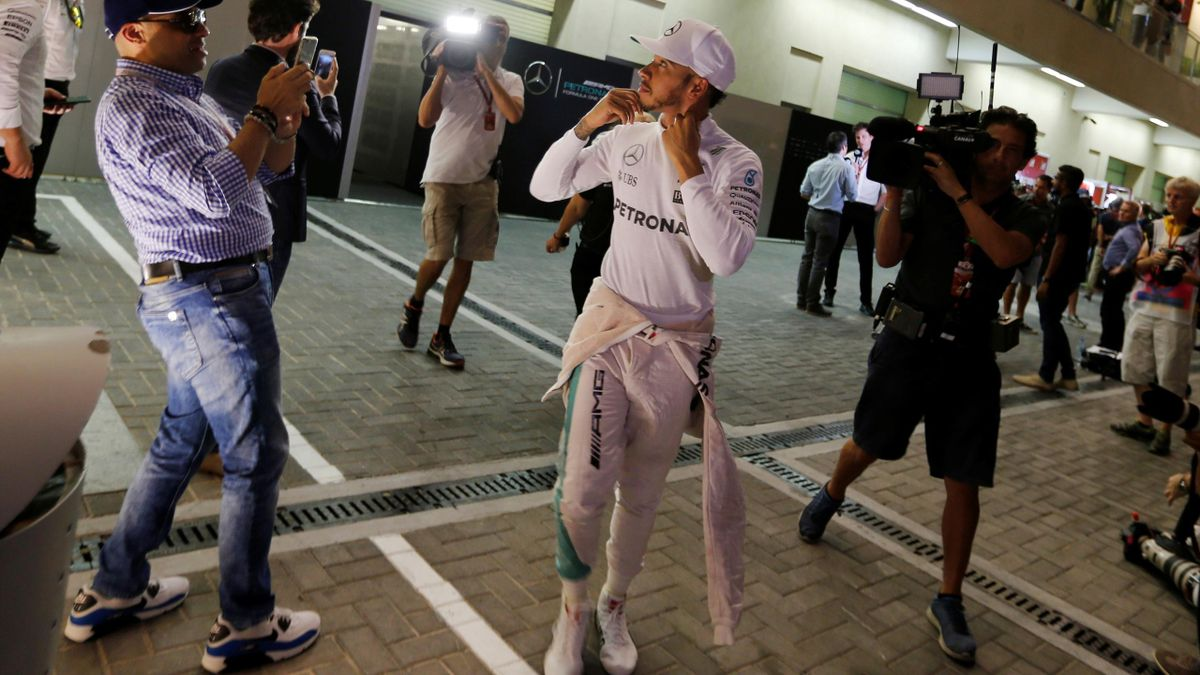 Mercedes' Formula One driver Lewis Hamilton of Britain (C) looks at a fan after the second free practice.
