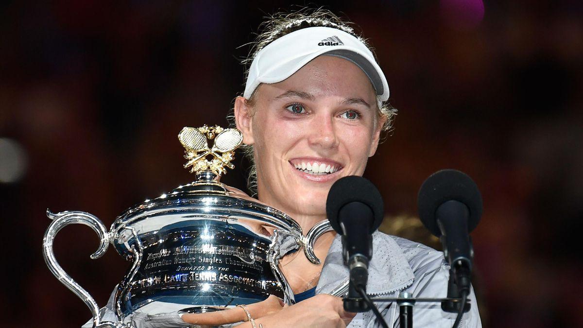 Denmark's Caroline Wozniacki poses with the winner's trophy after beating Romania's Simona Halep