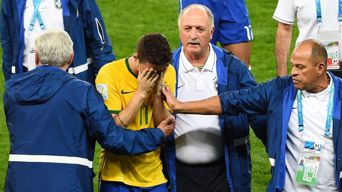 Head coach Luiz Felipe Scolari of Brazil and staff console Oscar after a 7-1 defeat to Germany during the 2014 FIFA World Cup Brazil Semi Final match between Brazil and Germany