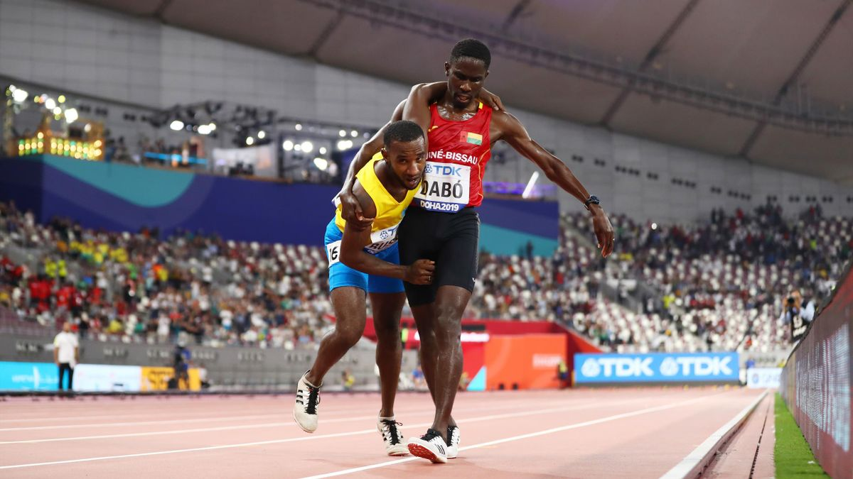 Braima Suncar Dabo of Guinea-Bissau helps Jonathan Busby of Aruba reach the finish line in the Men's 5000 metres heats during day one of 17th IAAF World Athletics Championships Doha 2019