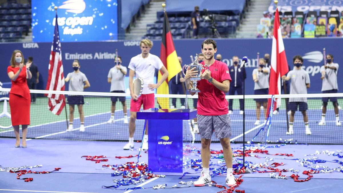 Dominic Thiem (R) of Austria celebrates with his championship trophy as Alexander Zverev (L) of Germany holds his finalist trophy
