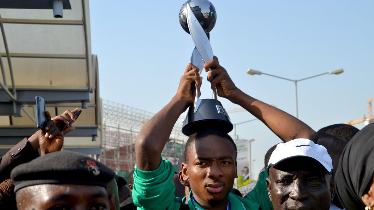 Nigeria's Kelechi Nwakali carries the Fifa Under-17 World Cup trophy on his head in the midst of a crowd gathered to receive the triumphant Nigeria U17 team, the Golden Eaglets, at Nnamdi Azikiwe Airport in Abuja, on November 11, 2015.