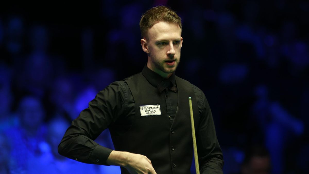Judd Trump of England chalks the cue during the semi-final match against Ronnie O'Sullivan