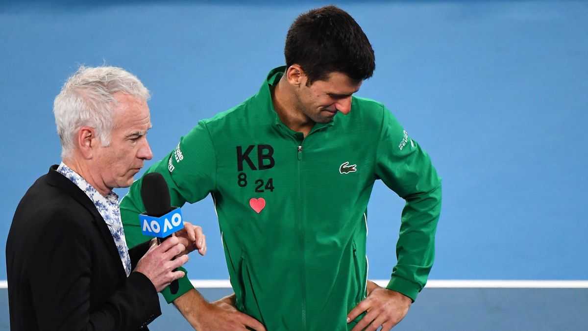 Serbia's Novak Djokovic gets emotional as he talks about Kobe Bryant next to former US tennis player John McEnroe after winning the men's singles quarter-final match against Canada's Milos Raonic