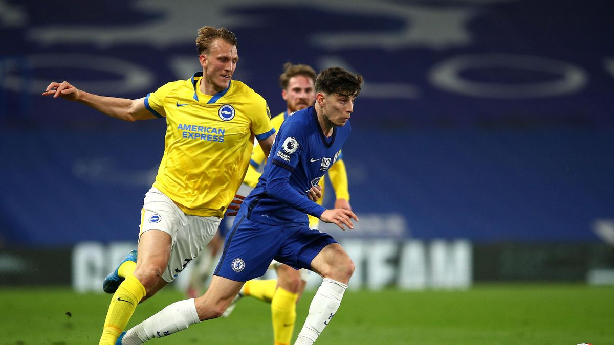 Kai Havertz of Chelsea runs with the ball under pressure from Dan Burn of Brighton and Hove Albion during the Premier League match between Chelsea and Brighton & Hove Albion at Stamford Bridge on April 20, 2021 in London, England