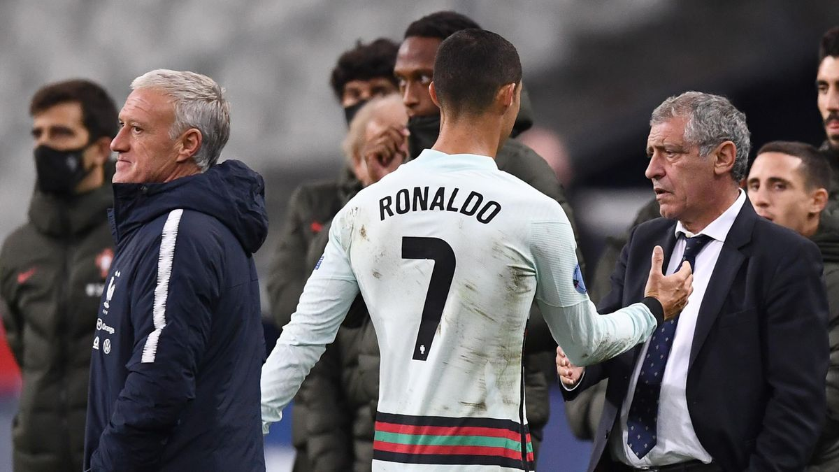 Portugal's forward Cristiano Ronaldo (C) shakes hands with Portugal's coach Fernando Santos (R) next to France's coach Didier Deschamps at the end of the Nations League football match between France and Portugal, on October 11, 2020 at the Stade de France