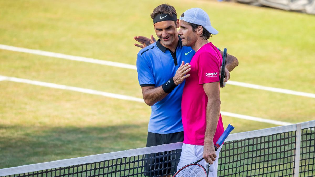 Roger Federer of Switzerland (L) congratulates Tommy Haas (R) of Germany