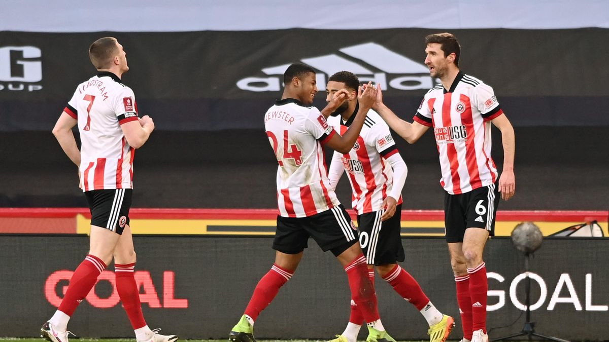 Chris Basham of Sheffield United celebrates with team mate Rhian Brewster after scoring
