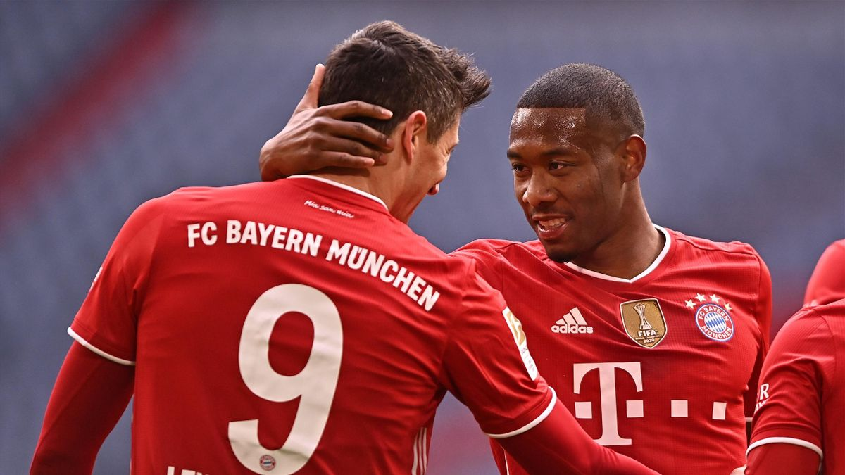 Robert Lewandowski of FC Bayern Muenchen celebrates with David Alaba after scoring their side's third goal during the Bundesliga match between FC Bayern Muenchen and VfB Stuttgart at Allianz Arena on March 20, 2021 in Munich, Germany.