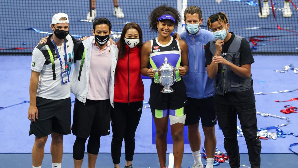 Naomi Osaka (3rd R) of Japan holds the trophy and celebrates with her team and boyfriend, rapper YBN Cordae (R), after winning her Women's Singles final match against Victoria Azarenka