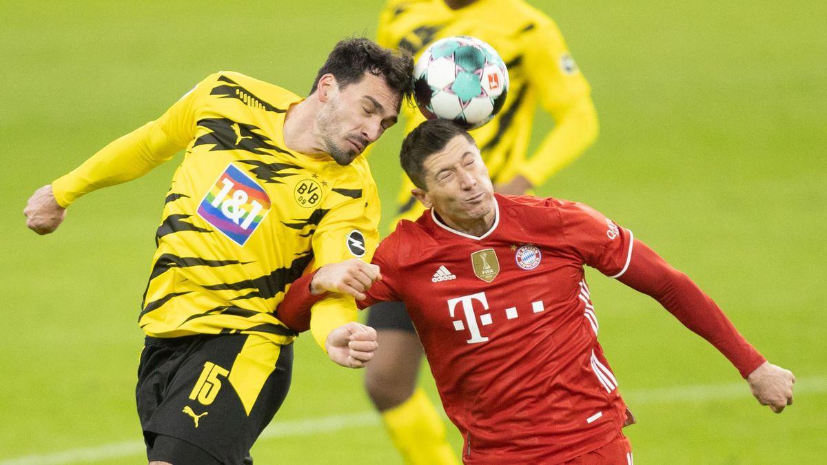 Mats Hummels of Borussia Dortmund and Robert Lewandowski of Bayern Munich battle for the ball
