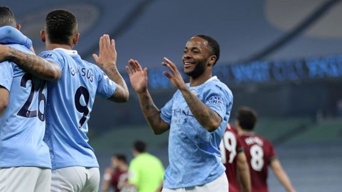 Manchester City's English midfielder Raheem Sterling (R) celebrates with teammates after an own goal by Wolverhampton Wanderers' Belgian midfielder Leander Dendoncker (unseen) during the English Premier League football match between Manchester City and Wo