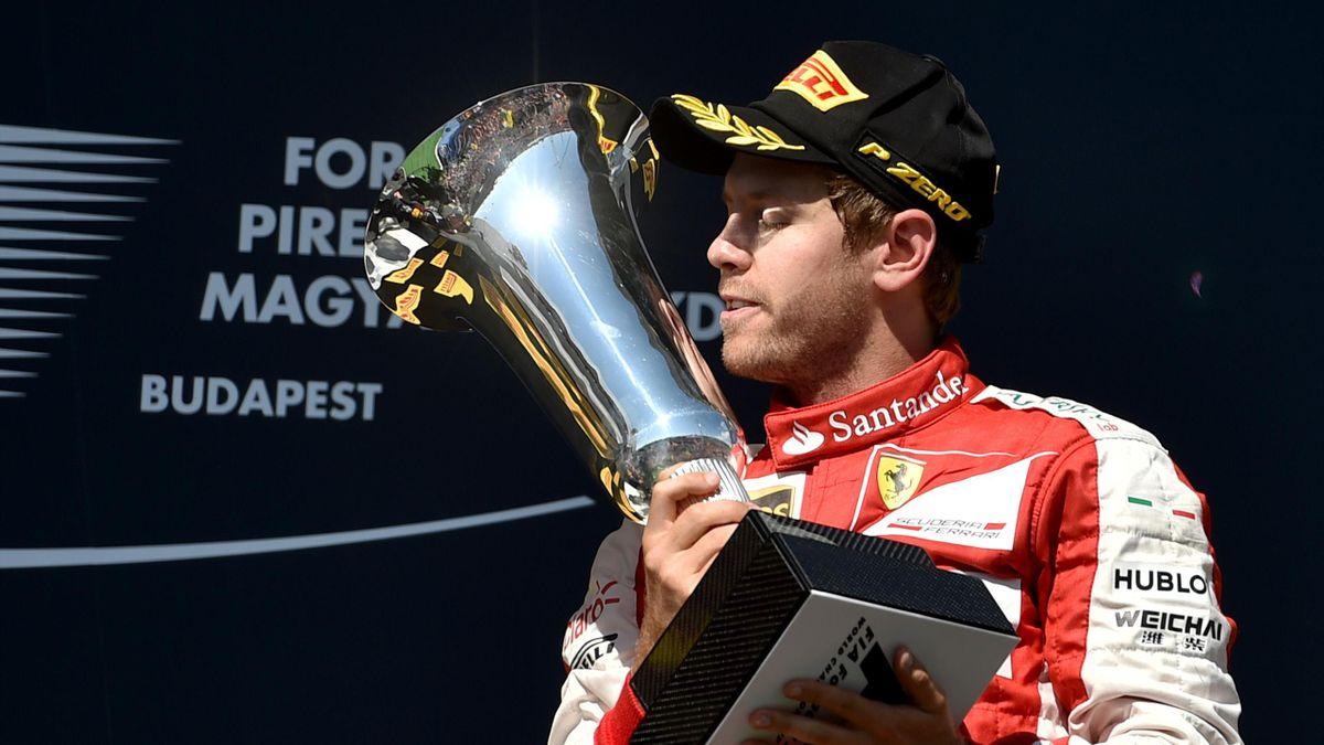 Ferrari's German driver Sebastian Vettel is to kiss the trophy as he celebrates on the podium winning the Hungarian Formula One Grand Prix at the Hungaroring circuit near Budapest on July 26, 2015