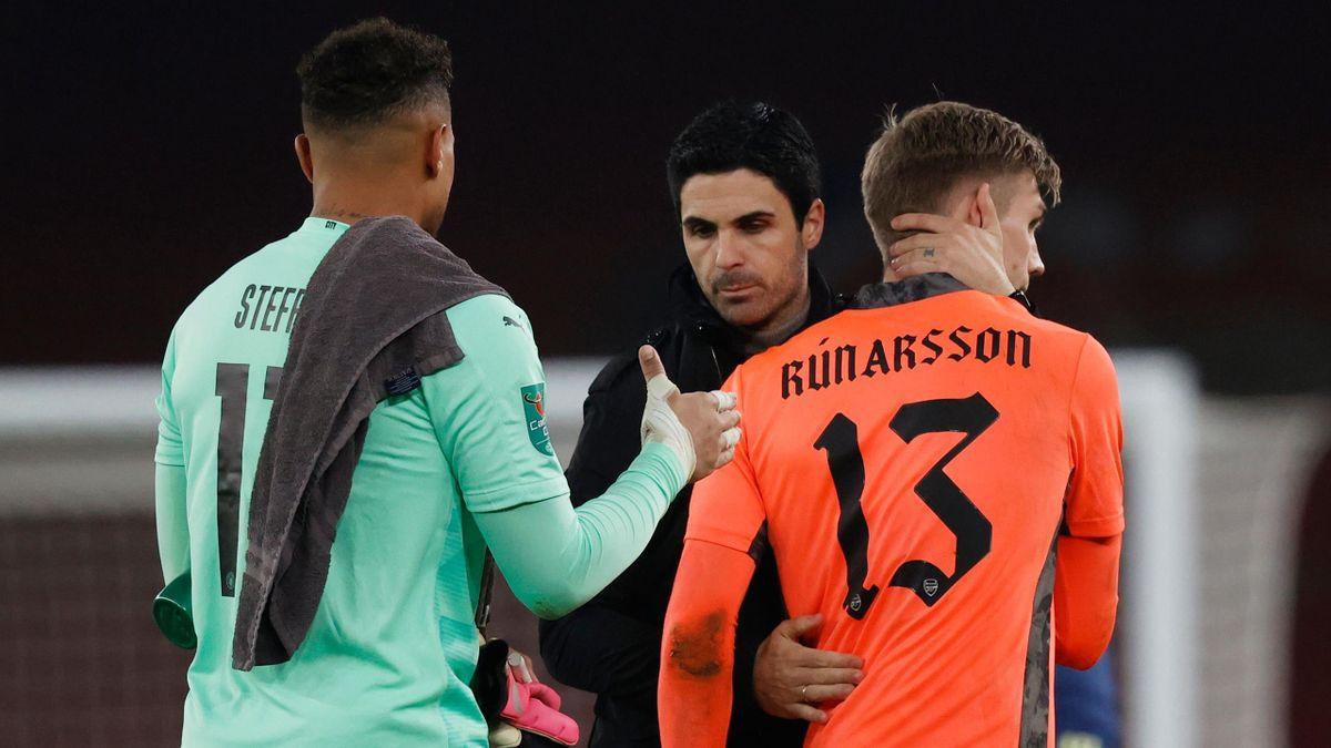 Mikel Arteta (C) consoles Arsenal's Icelandic goalkeeper Runar Alex Runarsson (R) after the English League Cup quarter final football match between Arsenal and Manchester City at the Emirates Stadium